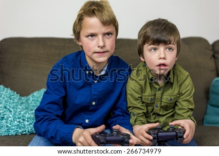 two little brothers on a couch,playing a computer game