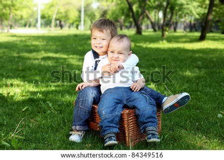 Two little brothers together in the summer park - stock photo