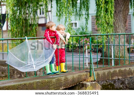 Two little brothers with big umbrella outdoors on rainy day. Kids boys having fun and wearing colorful waterproof clothes and rain boots. - stock photo