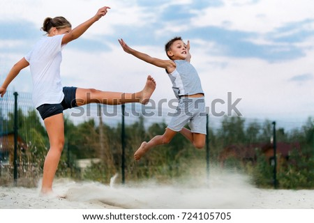 Two Little Caucasian Children Older Sister And Younger Brother Fighting Outdoor Girl Kicking