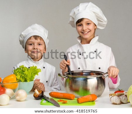 two little chefs in white uniform cook and smile