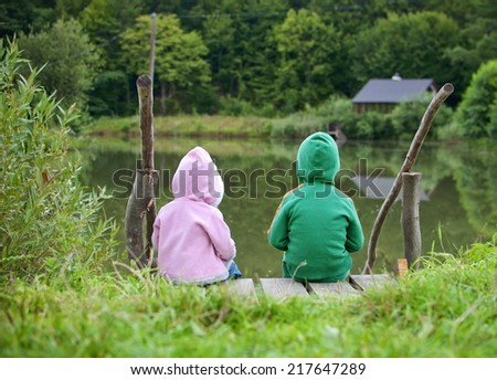 Two little child sitting together and looking at the lake view - stock photo