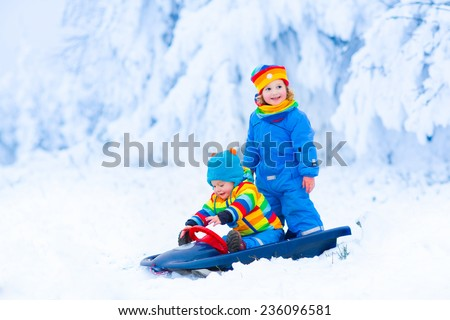 Two little children, adorable toddler girl and a funny baby boy, brother and sister, enjoying a sleigh ride playing in snow having fun in a snowy winter park - stock photo