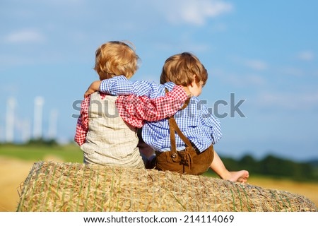 Two little children and friends sitting on hay stack or bale and speaking on yellow wheat field in summer - stock photo