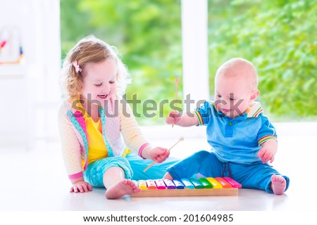 Two little children, brother and sister, cute curly toddler girl and a funny baby boy, having fun with colorful xylophone at a window, kids early development class, playing music - stock photo