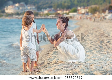 Two little children collecting seashells on the beach with their mother - stock photo