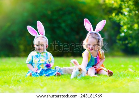 Two little children, cute curly toddler girl and funny baby boy wearing bunny ears having fun at Easter egg hunt playing with basket and toy rabbit in a sunny spring garden - stock photo
