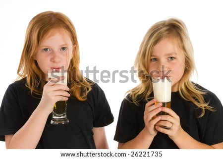 Two little children drinking a glass of beer - stock photo
