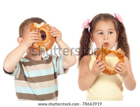 Two little children eating bagels - stock photo