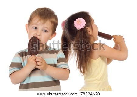 Two little children eating chocolate ice cream - stock photo