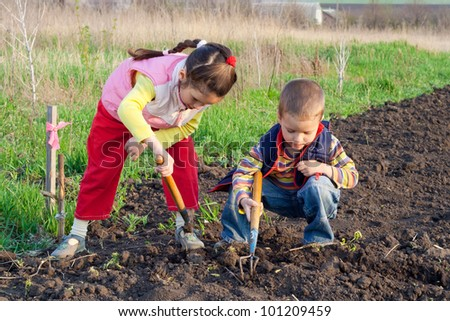 Two little children planting seeds and weed beds in the field - stock photo