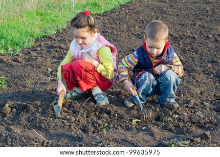 Two little children planting seeds and weed beds in the garden - stock photo