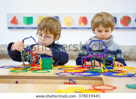 Two little children playing with lots of colorful plastic blocks kit indoor. kid boys having fun with building and creating geometric figures.