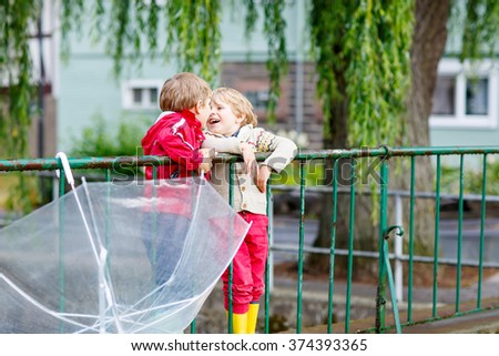 Two little children with big umbrella outdoors on rainy day. Kids boys having fun and wearing colorful waterproof clothes and rain boots. - stock photo