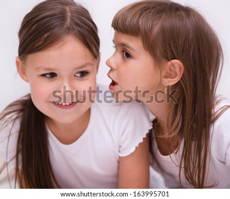 Two little cute girls are chatting - stock photo