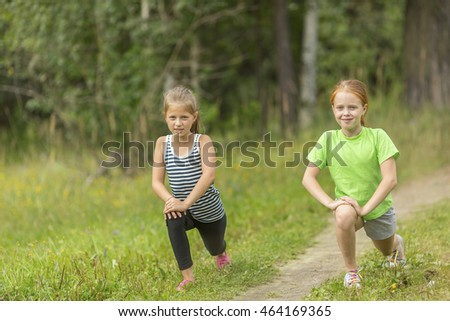 Two little cute girls warming up outdoors. Morning exercises.