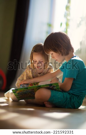 Two little cute kids reading a book sitting on the floor. Happy family. - stock photo