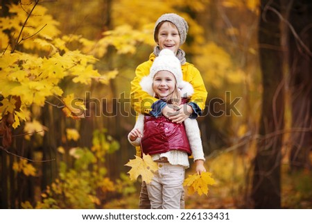 Two little cute smiling kids in bright jackets walking together in a park on a sunny autumn day. Friendship between siblings. Happy family concept