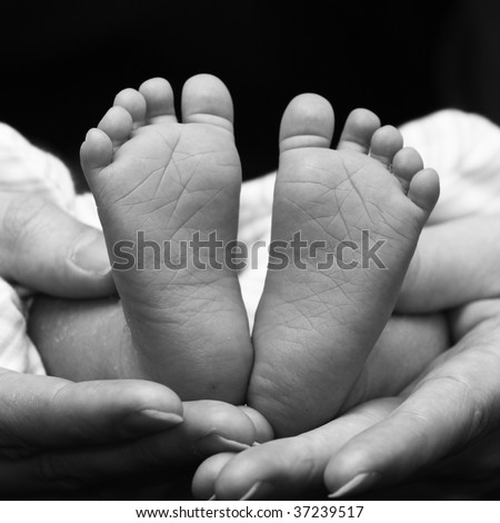 two little feet in the shape of heart in cuddling hands - stock photo