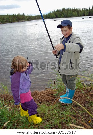 Two little fishers catches a fish