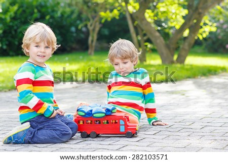 Two little friends boys in colorful clothing with stripes playing with red school bus and toys in summer garden on warm sunny day. Learning to play and communicate together. - stock photo