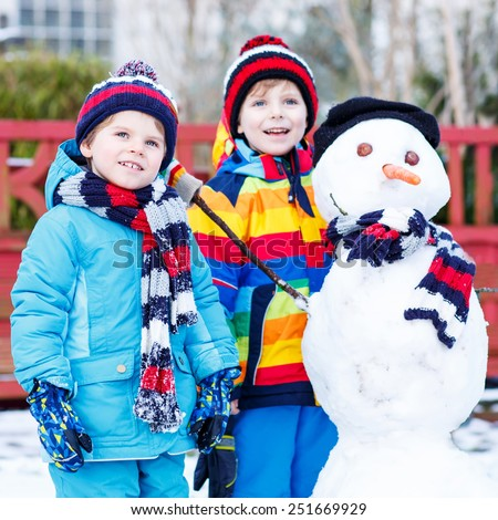 Two little friends making a snowman, playing and having fun with snow, outdoors  on cold day. Active outoors leisure with children in winter. - stock photo