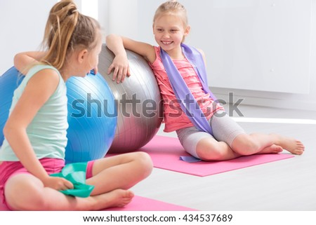 Two little friends resting against large exercise balls after finished exercises, smiling and chatting