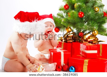 Two little friends  sitting beside Christmas tree - stock photo