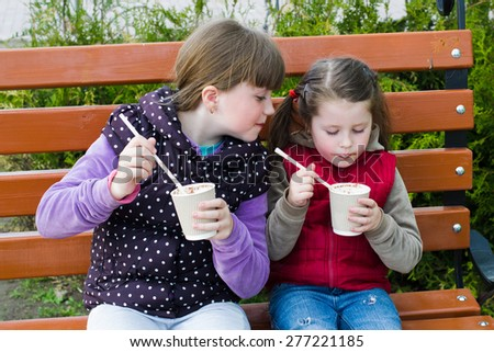 two little funny girl drinking cocoa on a park bench - stock photo