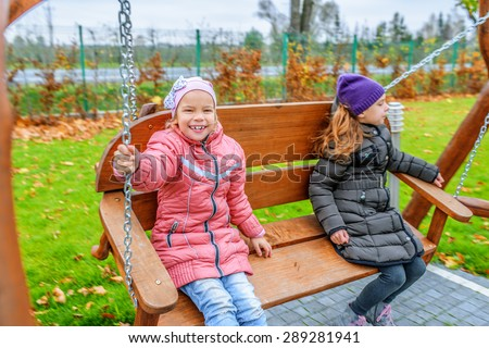 two little funny girls swinging on playgroud speaking with each other - stock photo