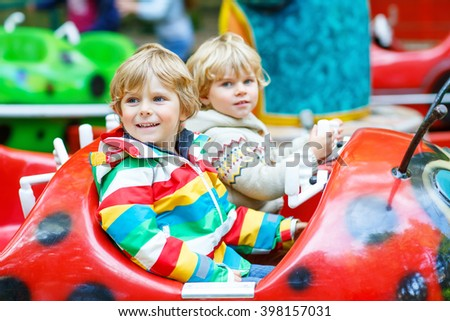 Two little funny kid boys riding on ladybug on roundabout carousel in amusement park. Happy children, friends having fun outdoors on sunny day.