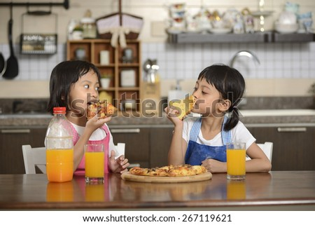 Two little girl eating pizza on the dining room - stock photo