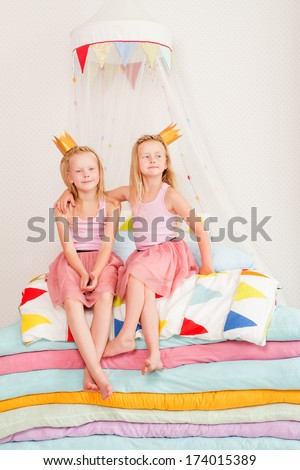 "Two little girl lying on a pile of mattresses. the fairy tale ""the princess on a pea"""