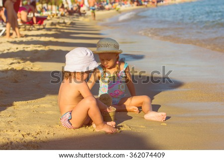 Two Little Girl, Playing on the beach, at the Aegean Sea.