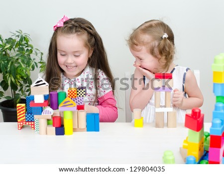 Two little girl playing with building blocks - stock photo