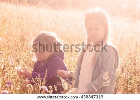 Two little girl playing with dandelion on the meadow ,sunlight in background.