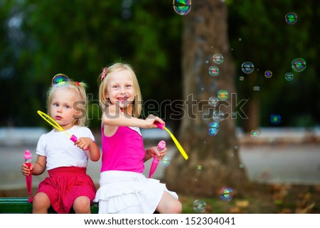Two little girl playing with spoon bubbles - stock photo