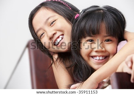 two little girl showing their affection posing to camera - stock photo