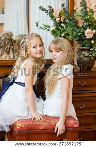 Two little girl sitting at mirror in bed room preparing for party - stock photo