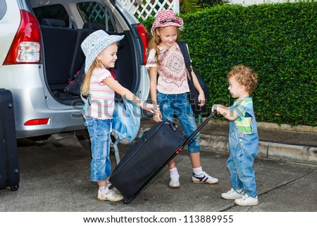 two little girls  and boy standing near the car with backpacks - stock photo