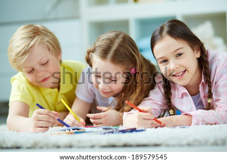 Two little girls and cute boy lying on the floor and drawing