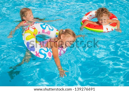 two little girls and little boy playing in the pool with rubber rings - stock photo