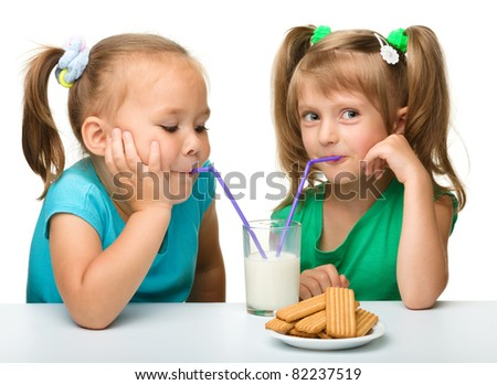 Two Little girls are drinking milk from one glass using straw, isolated over white - stock photo