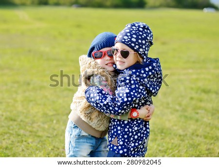 two little girls are hugging in spring field - stock photo