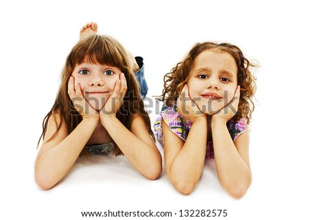 Two little girls are lying on the floor with his head in his hands. Isolated on white background - stock photo