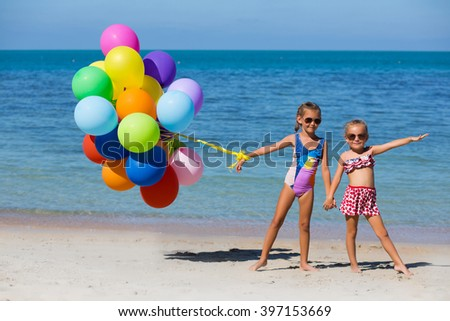 Two little girls are playing and smiling on the beach with color - stock photo