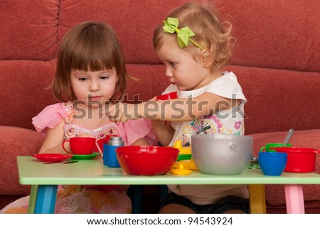 Two little girls are playing at the table - stock photo
