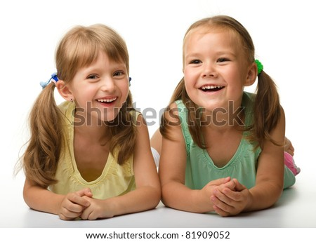 Two little girls are playing, isolated over white - stock photo