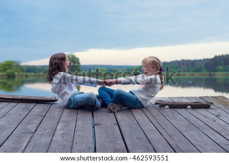 two little girls are resting on the dock by the lake