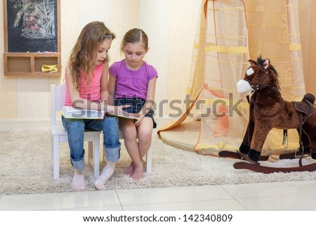 Two little girls are sitting in the game room on the chairs and read a book, Anya 7 years and 6 years old Jeanette. - stock photo